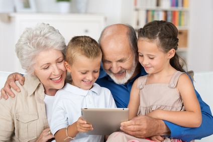 großeltern und enkel schauen auf tablet-pc